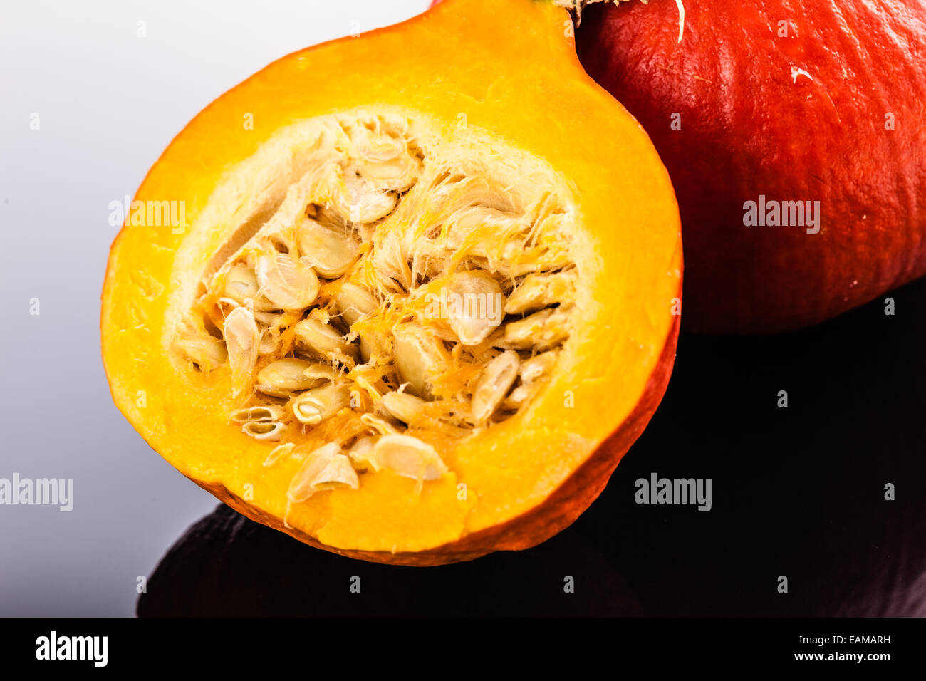 Half Red kuri squash, a small japanese  pumpkin with reflection over a glass background Stock Photo