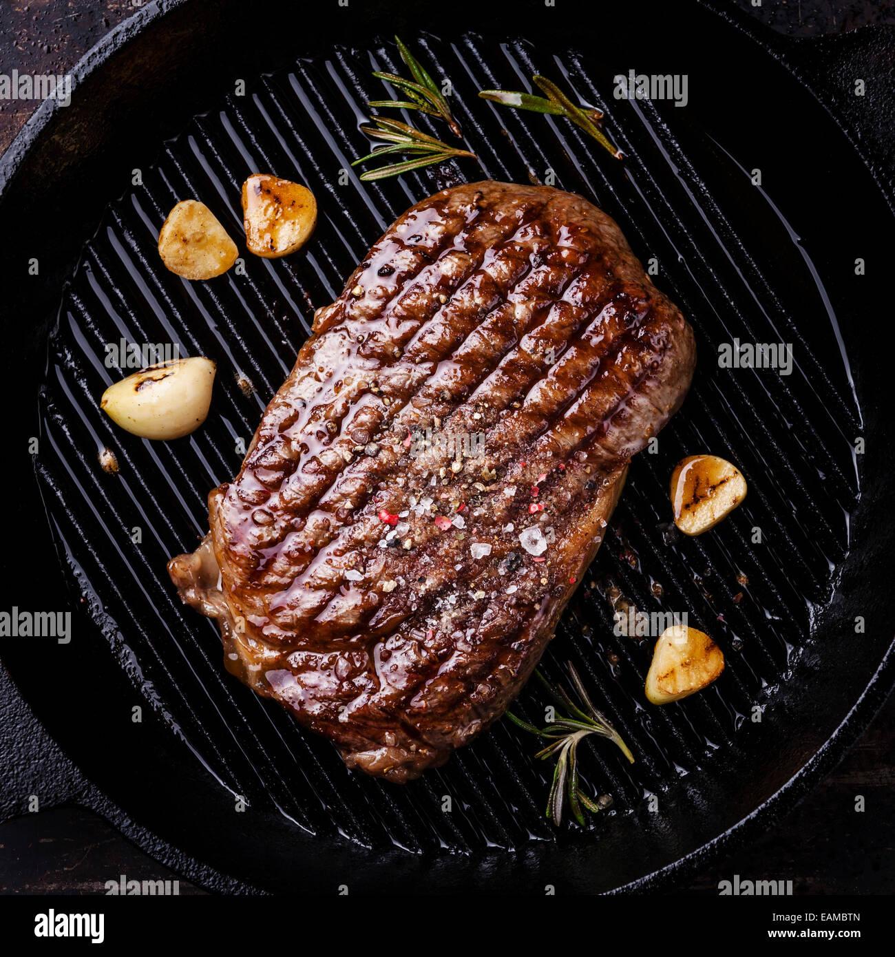 Grilled Ribeye steak on grill pan on dark background - Stock Image