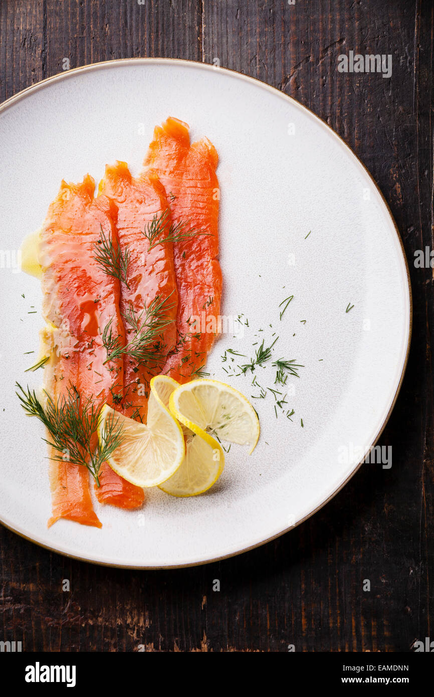 Smoked Salmon with dill and lemon on white plate - Stock Image