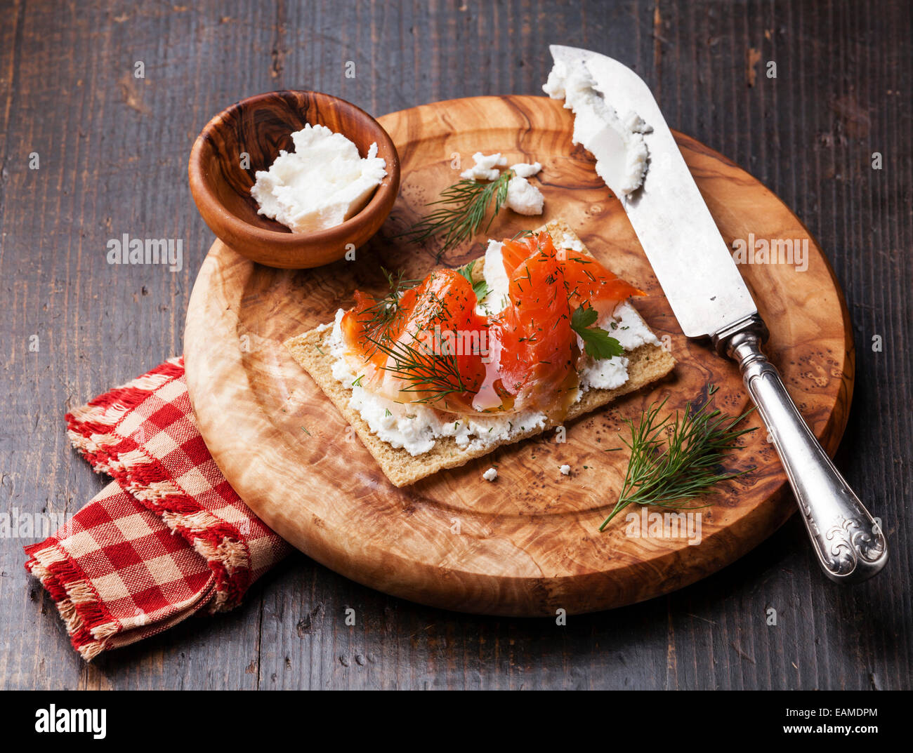 Sandwich on Crisp bread with Smoked salmon and soft Cream cheese on Olive wood plate Stock Photo