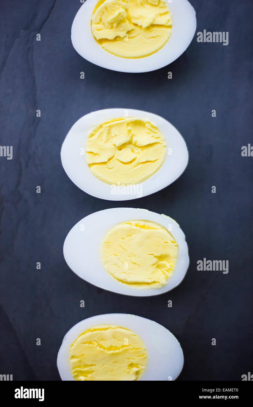 Hard Boiled Duck Egg Halves on Blue Slate - Stock Image