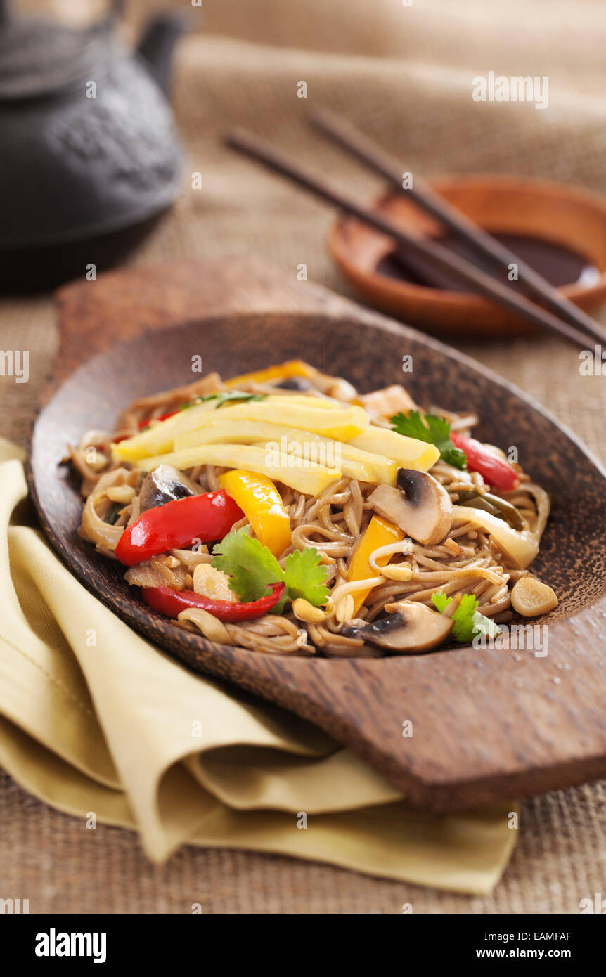 Asian yakisoba noodle with fried vegetables and omelette on a wooden plate - Stock Image