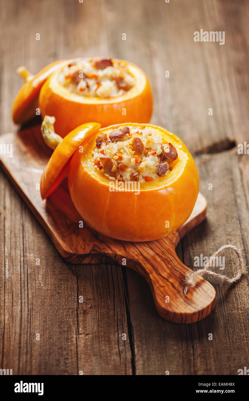 Little roasted pumpkins stuffed with chicken meat, vegetables and rice - Stock Image