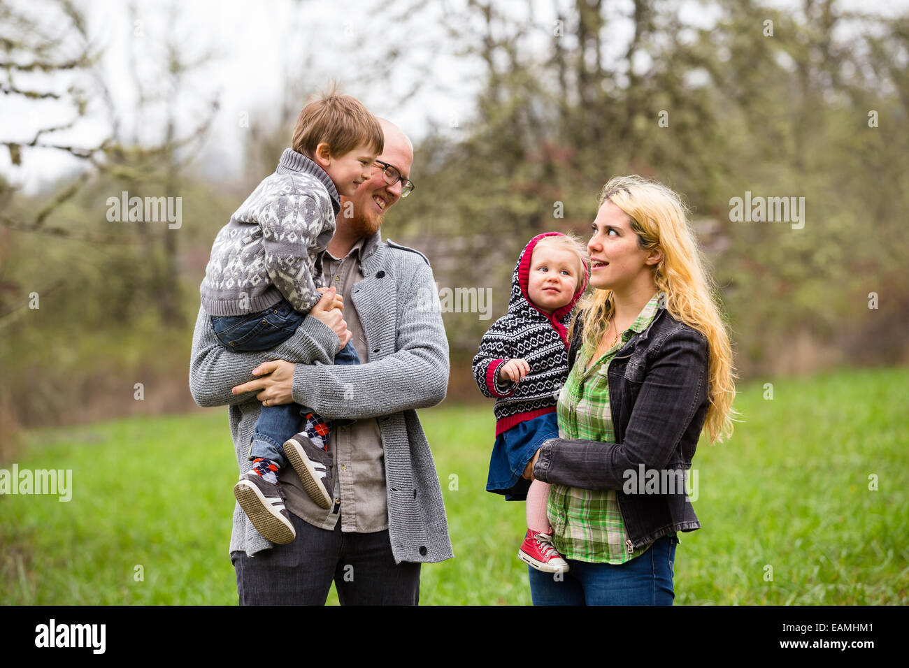 Lifestyle portrait of a family of four including a mother, father, son, and daughter interacting showing happiness. - Stock Image