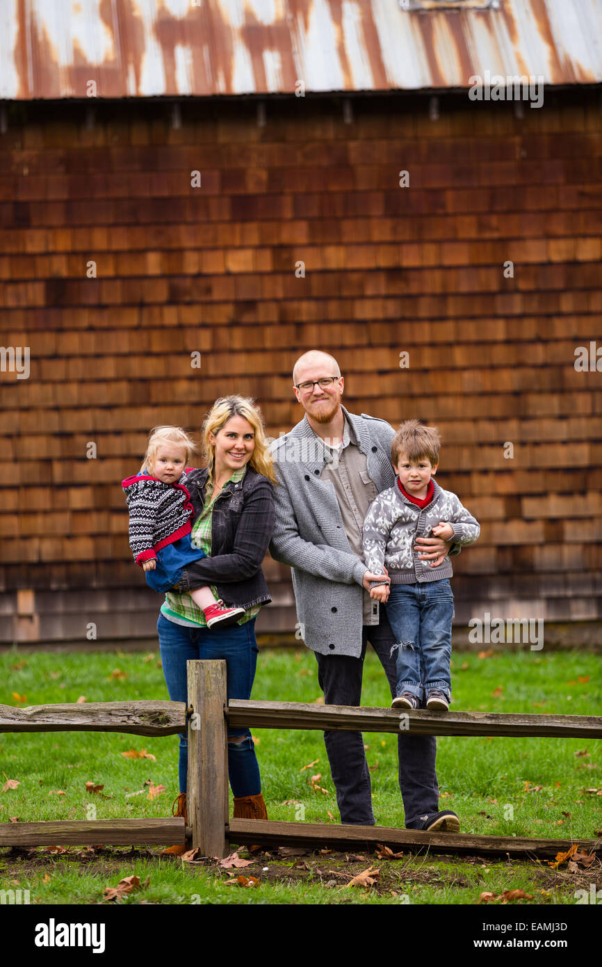 Family lifestyle portrait of a mother, father, son and daughter in front of a rustic barn in the country. - Stock Image
