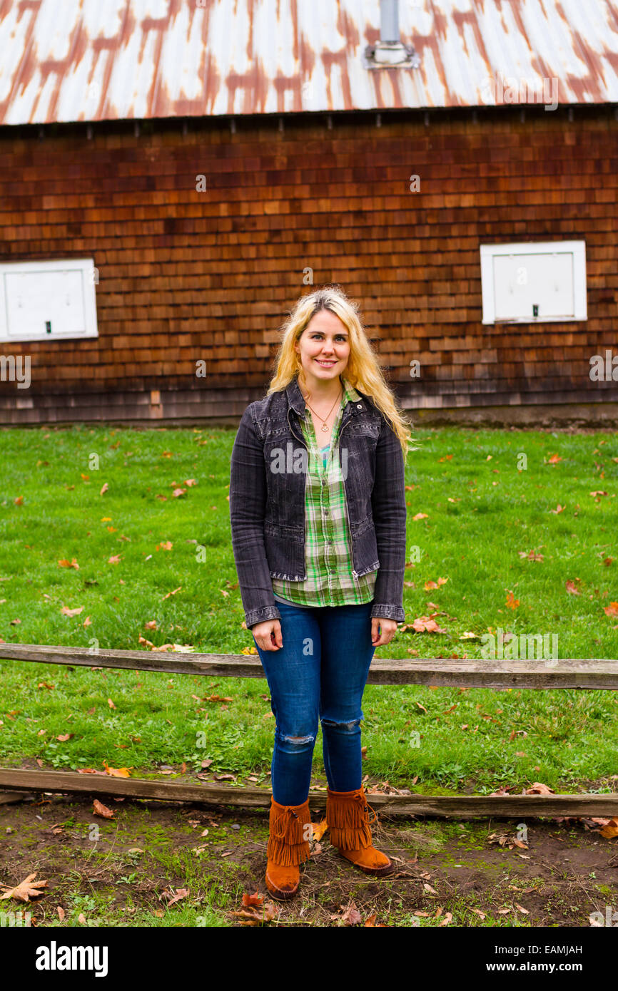 Lifestyle portrait of a woman outdoors with a barn in the background. - Stock Image