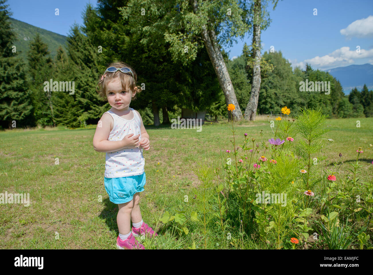 A Pretty Little Girl Playing With Flowers In The Garden And She Look