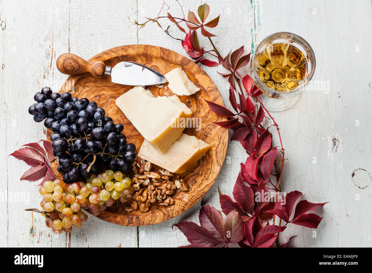 Parmesan cheese and grapes on olive wood plate and wine - Stock Image