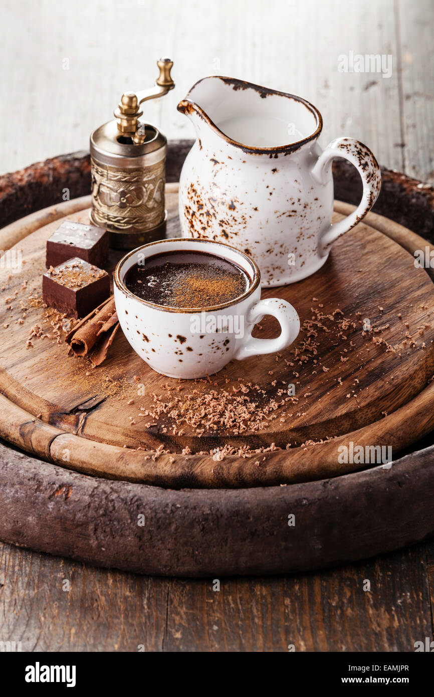 Hot chocolate sprinkled with cinnamon on dark wooden background - Stock Image