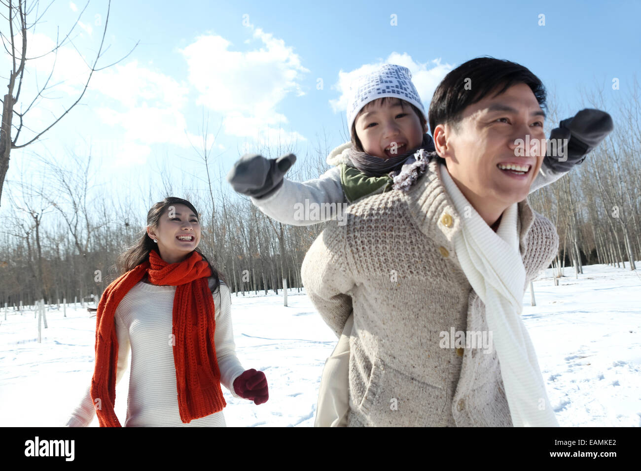 A family of three running in the snow - Stock Image