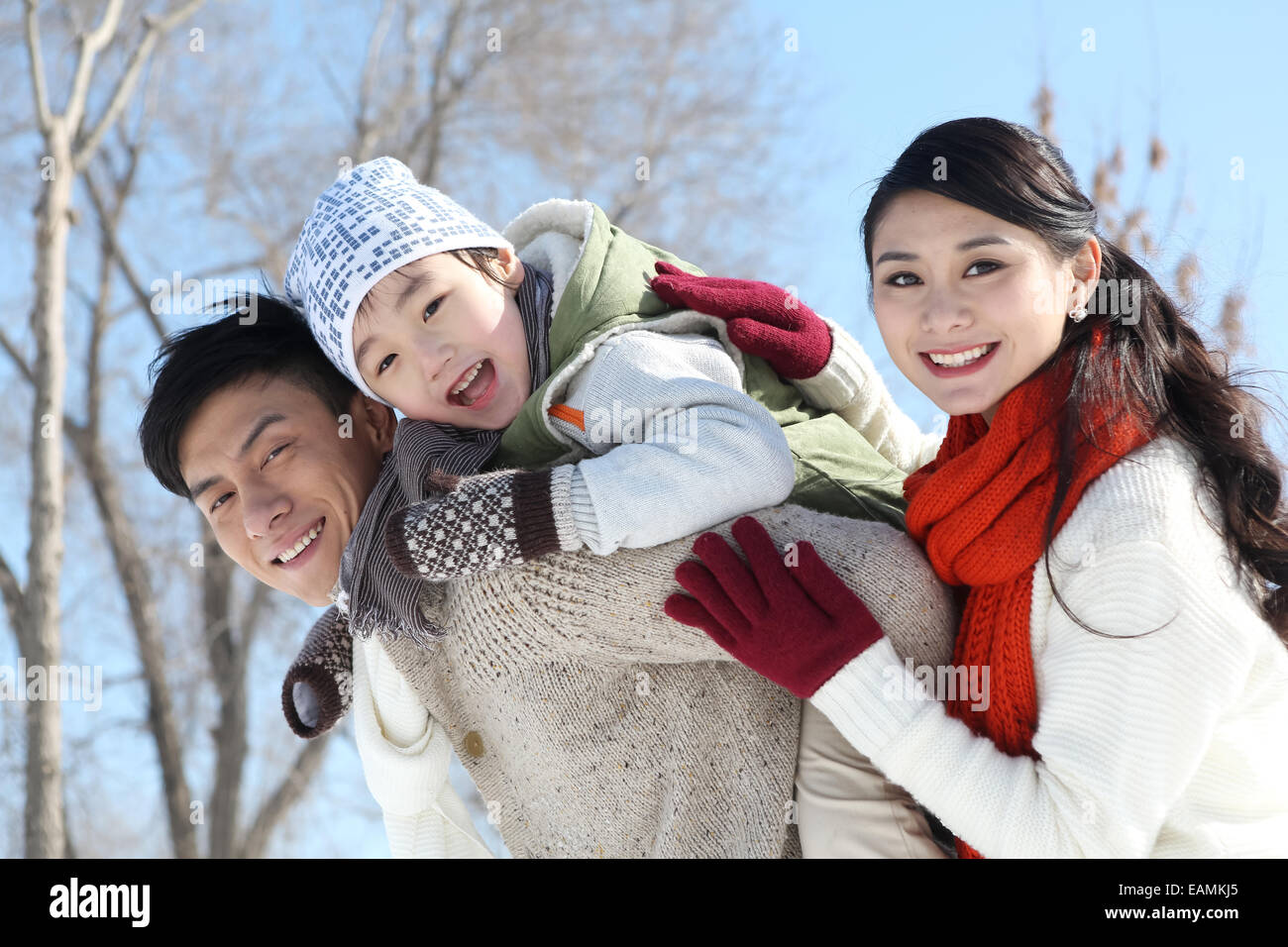 Mother and father carrying his son in the outdoors - Stock Image