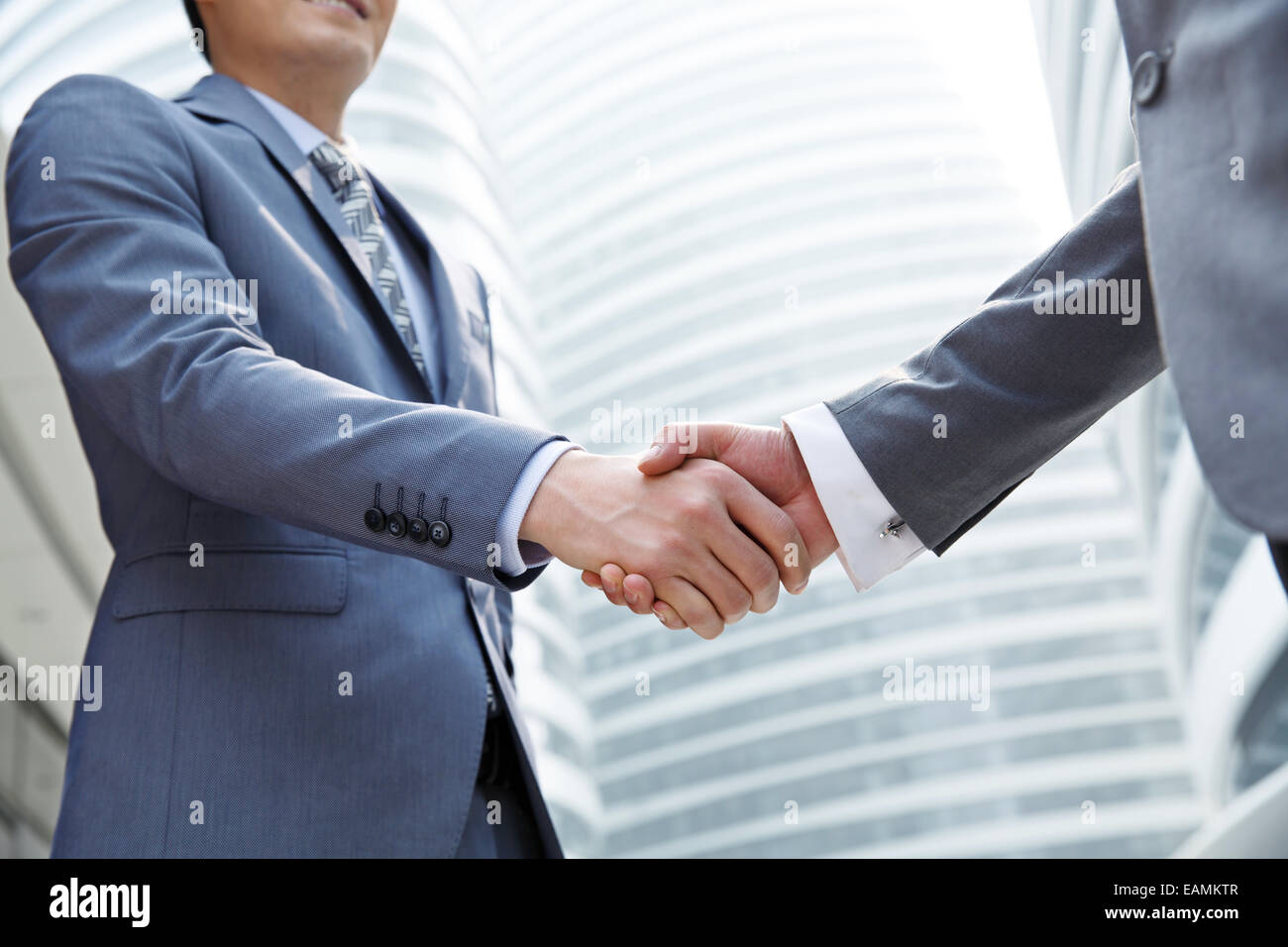 the two eastern business people shake hands stock photo