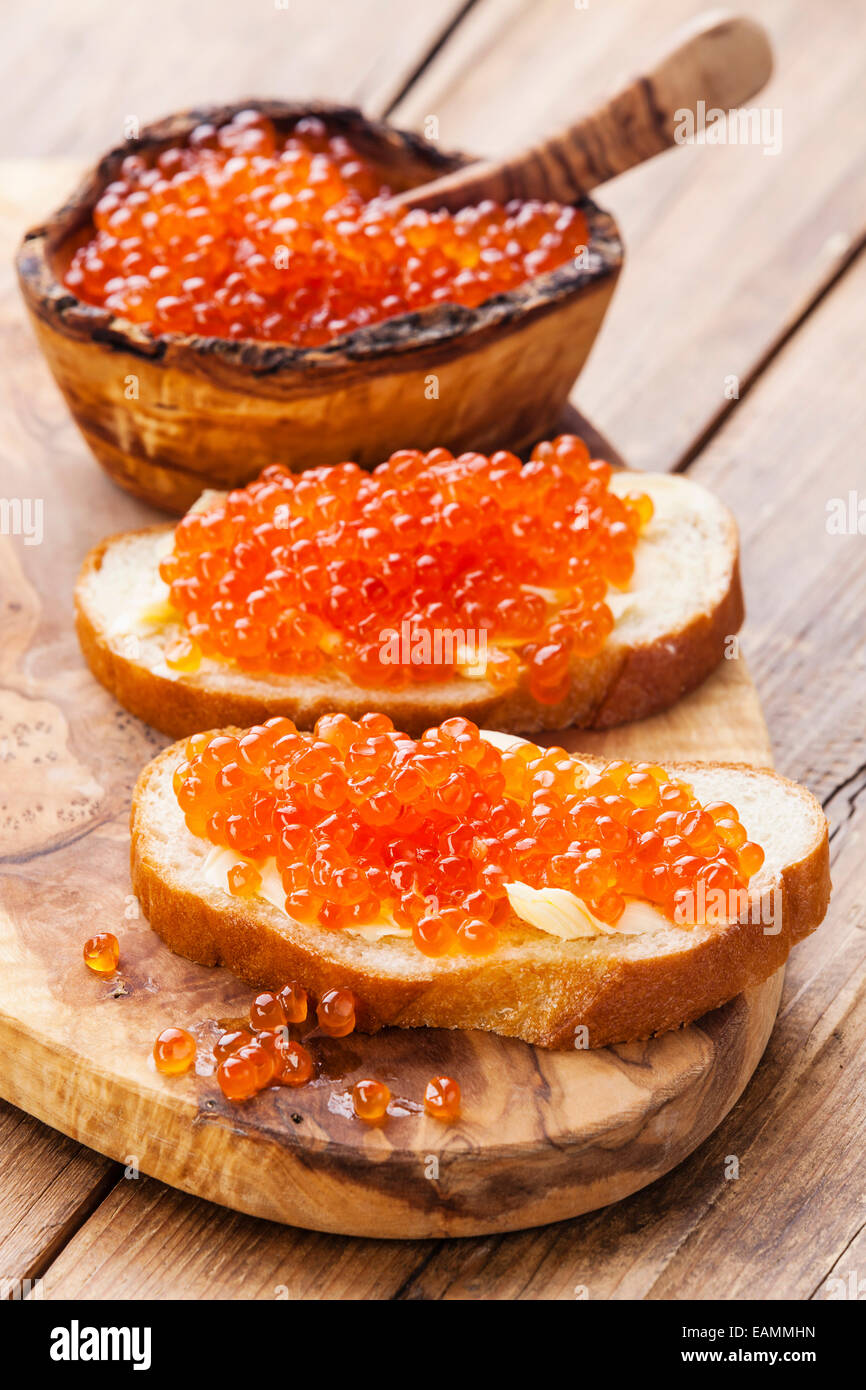 Sandwiches with Salmon red caviar on wooden background - Stock Image