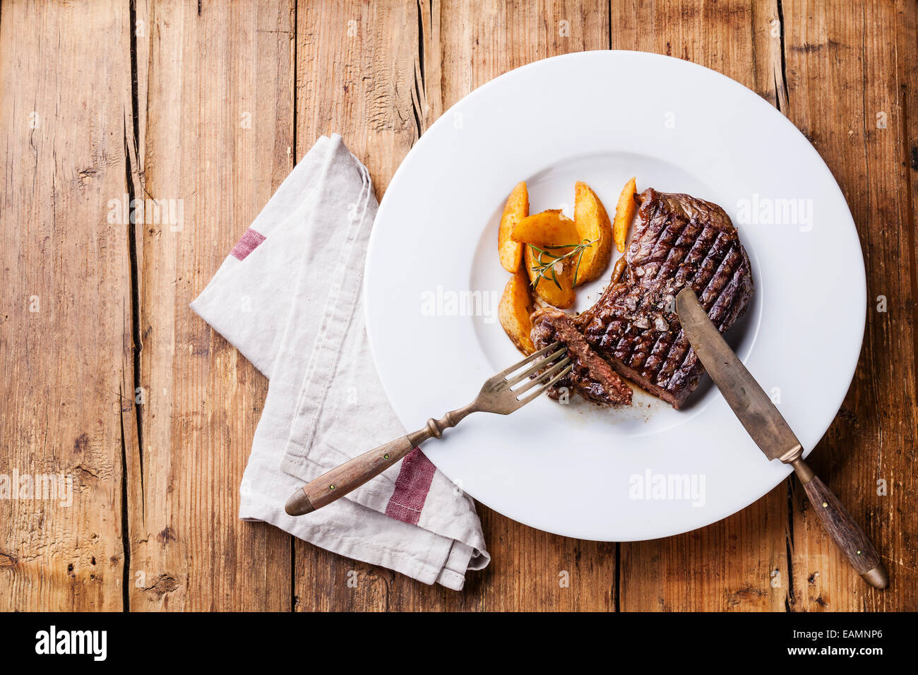 Grilled South American premium beef New York steak with roasted potato wedges on white plate on wooden background - Stock Image