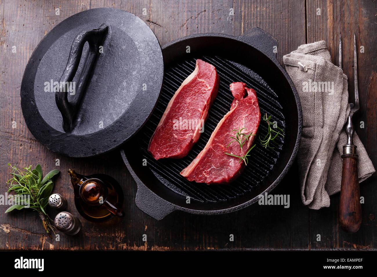 Rare Striploin steak on grill pan on wooden background - Stock Image