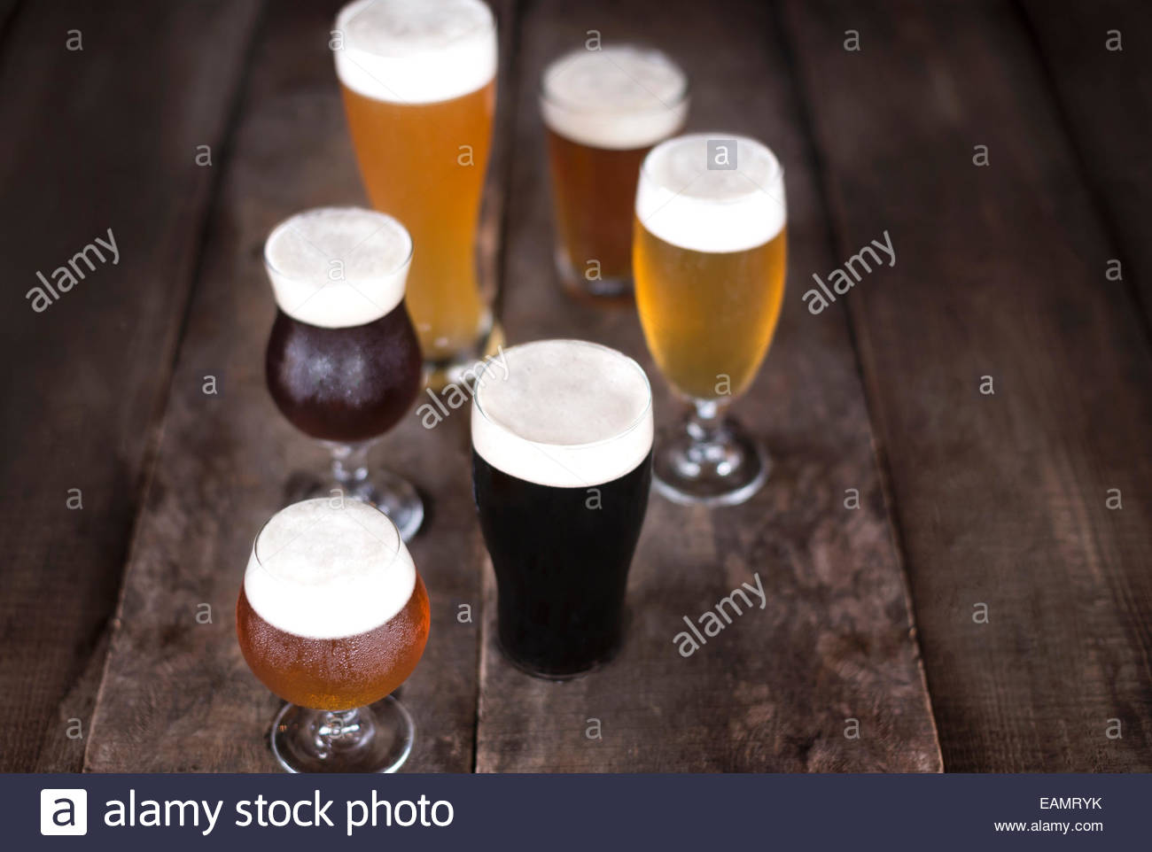 Variety of beers in a variety of glassware on a rustic wood surface. - Stock Image