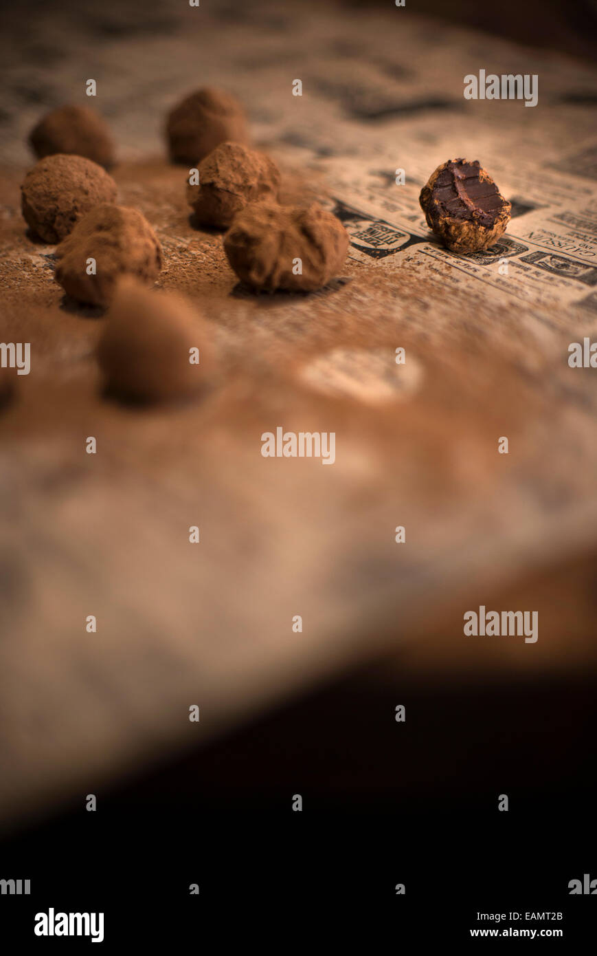 Rows of chocolate truffles covered in cocoa on antique newspaper and rustic wood surface. One truffle bitten into. - Stock Image