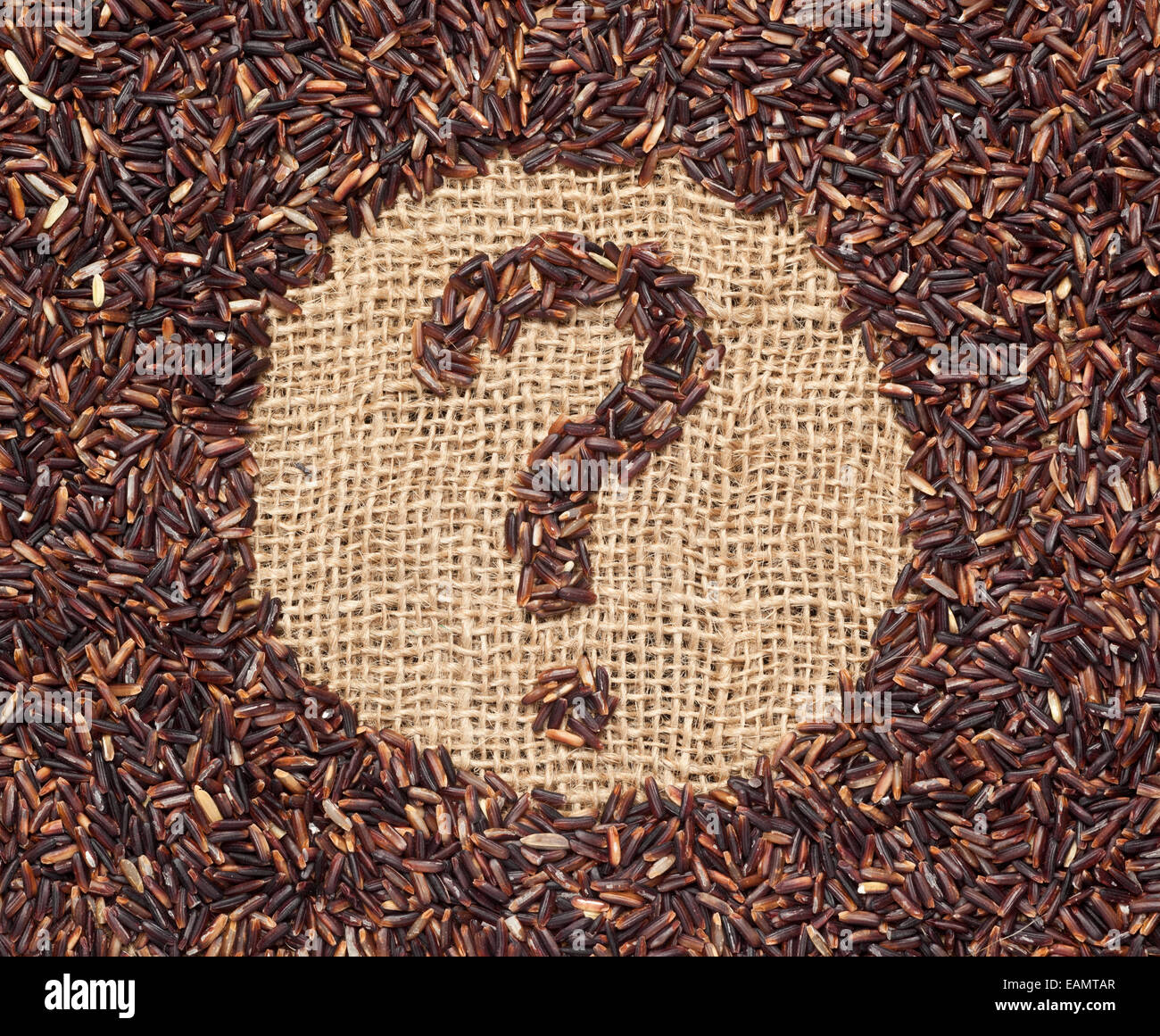Red rice forming a question mark on burlap fabric - Stock Image