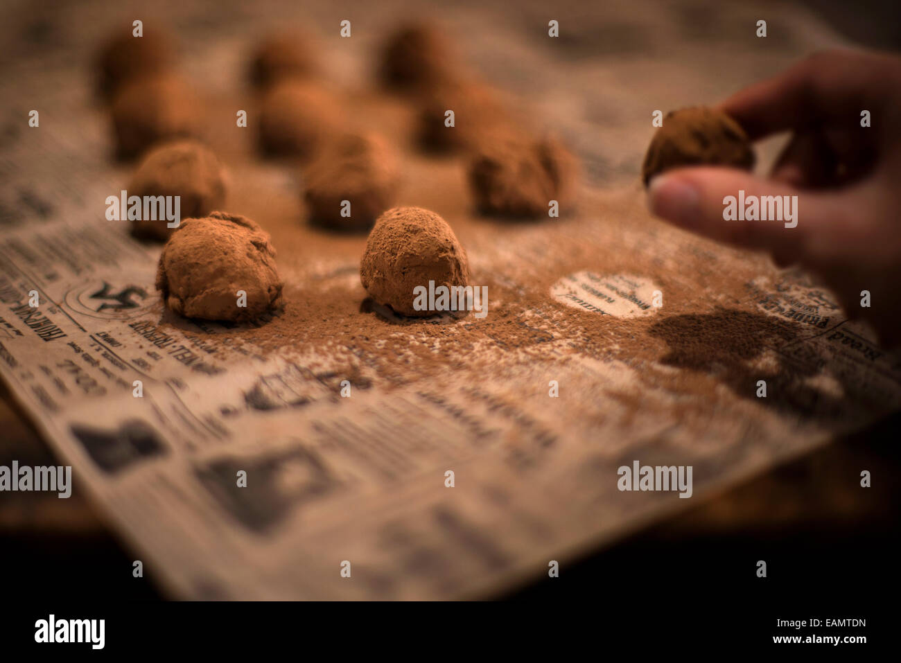 Rows of chocolate truffles dusted with cocoa powder on antique newspaper and rustic wood surface. One truffle being - Stock Image