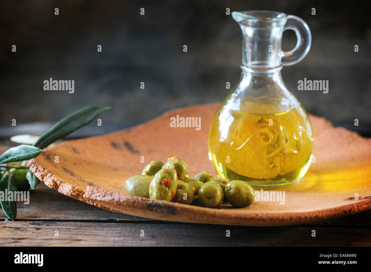 Green olives and bottle of olive oil served in handmade clay plate over wooden table. - Stock Image