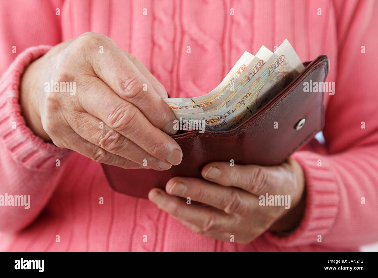 Elderly senior woman old age pensioner taking ten pound notes GBP out of a money wallet to buy and pay for something - Stock Image