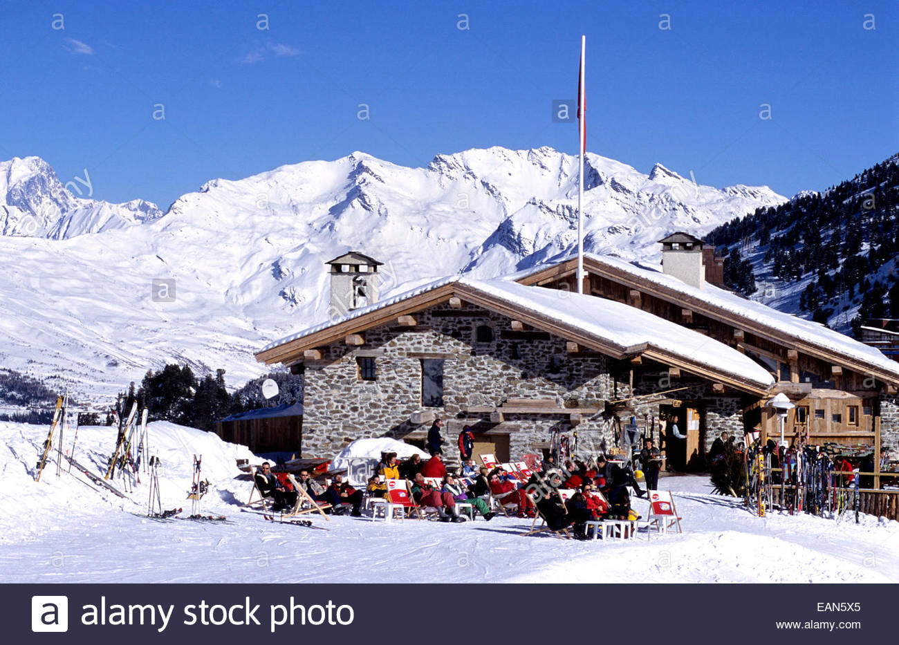 People sunbathing on a outdoor cafe. Les Arcs village. Savoie, France. - Stock Image