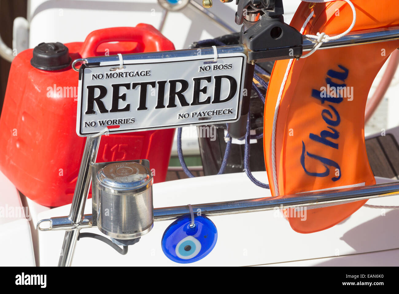 Retired sign on yacht. Sign says: No Mortgage, No Boss, No Worries and No Paycheck - Stock Image