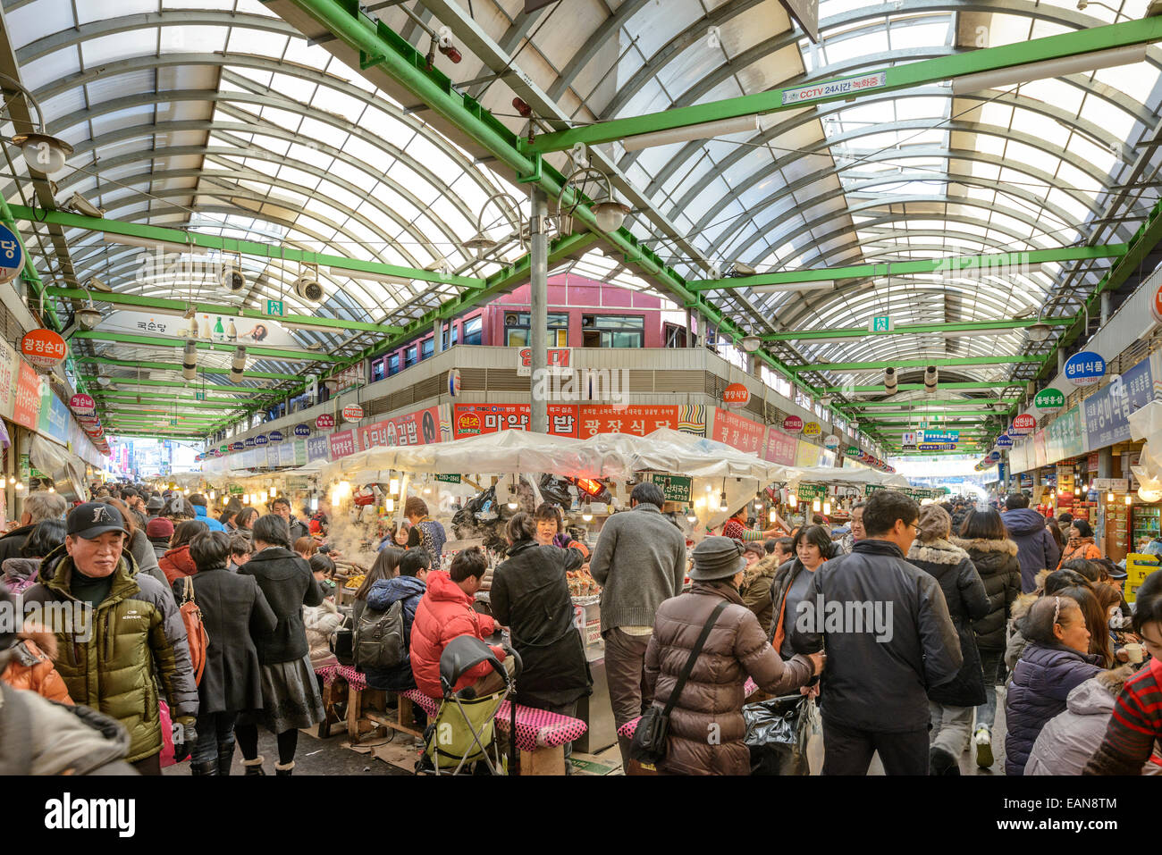 Shoppers in Seoul, South Korea pass through Gwangjang Traditional Market. - Stock Image