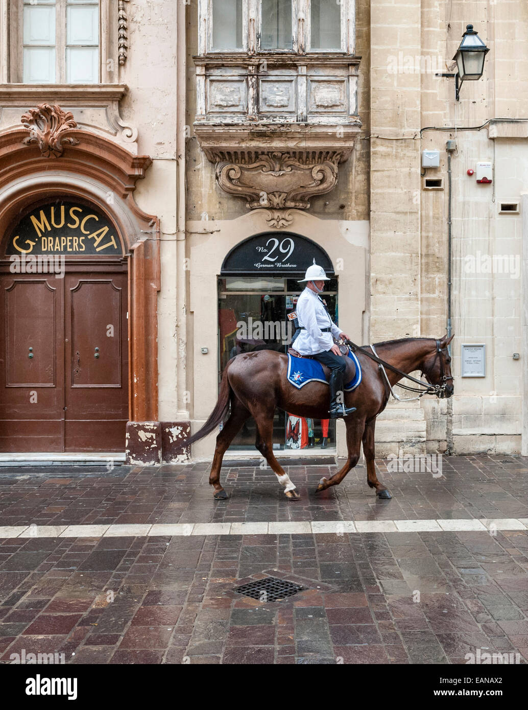 Valletta, Malta. A mounted policeman riding through the street past old shops - Stock Image