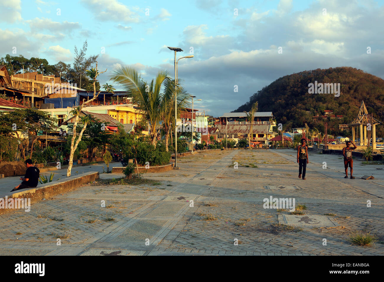 People on unkempt waterfront promenade in Labuan Balo, Flores - Stock Image