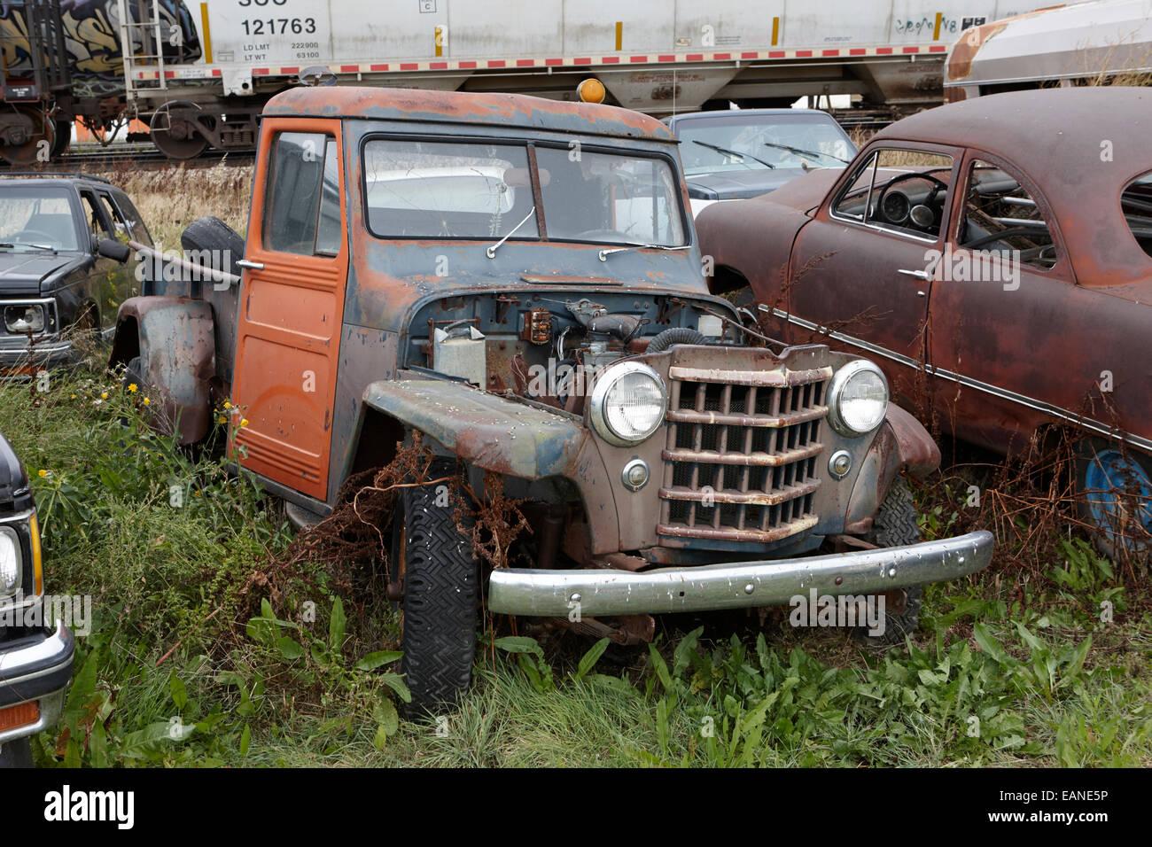 vintage historic jeep one ton pickup vehicles in junkyard Saskatchewan Canada - Stock Image