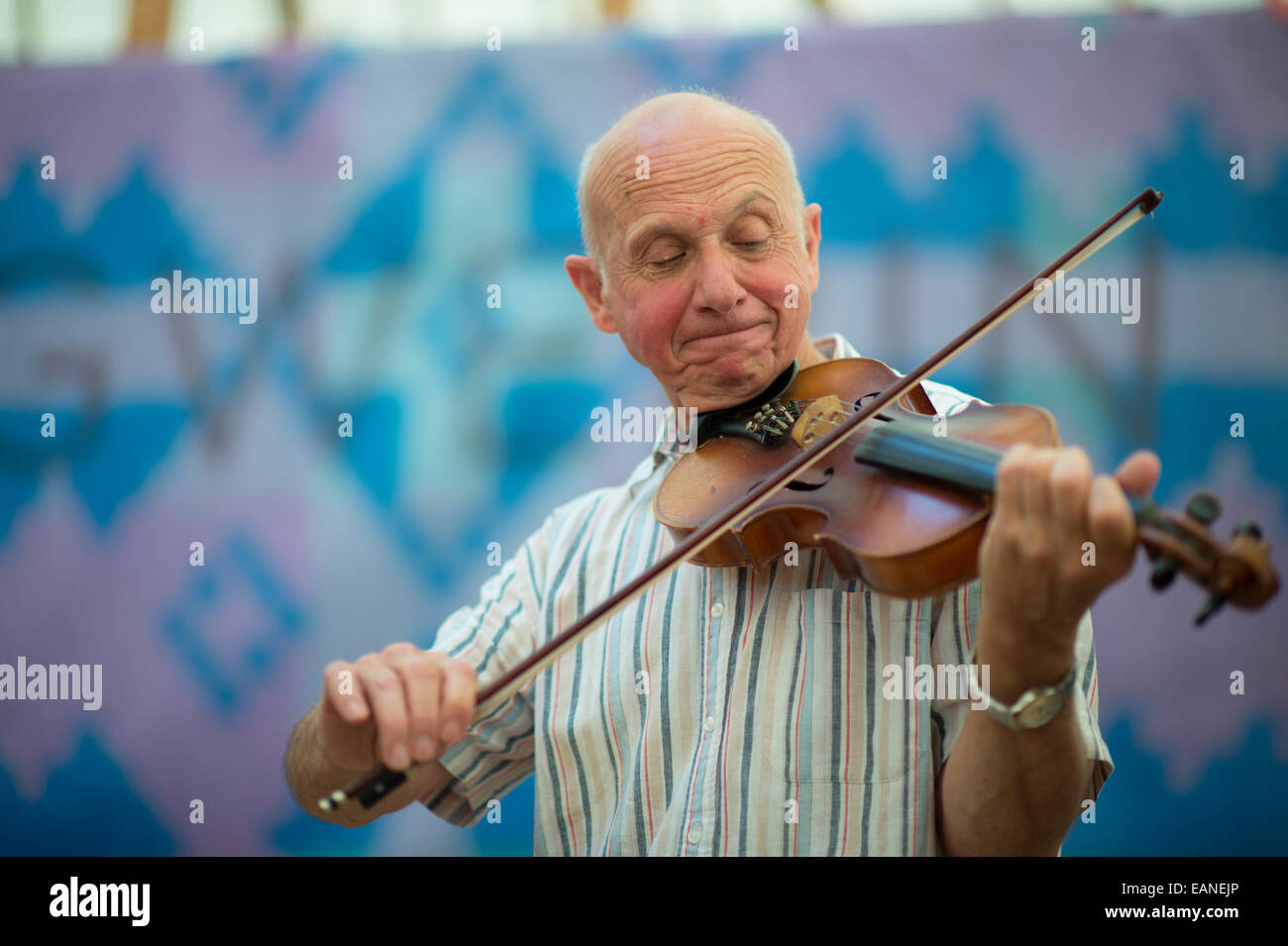 A senior man adult male  playing traditional folk music on the violin at the National Eisteddfod of Wales, Llanelli, - Stock Image