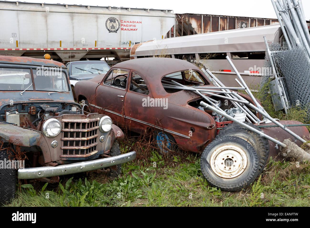 vintage historic jeep one ton pickup and sedan vehicles in junkyard Saskatchewan Canada - Stock Image