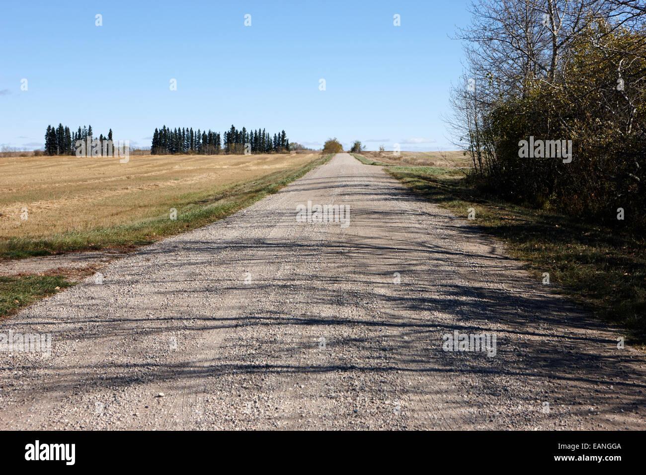 rough rural unpaved gravel road in remote Saskatchewan Canada - Stock Image