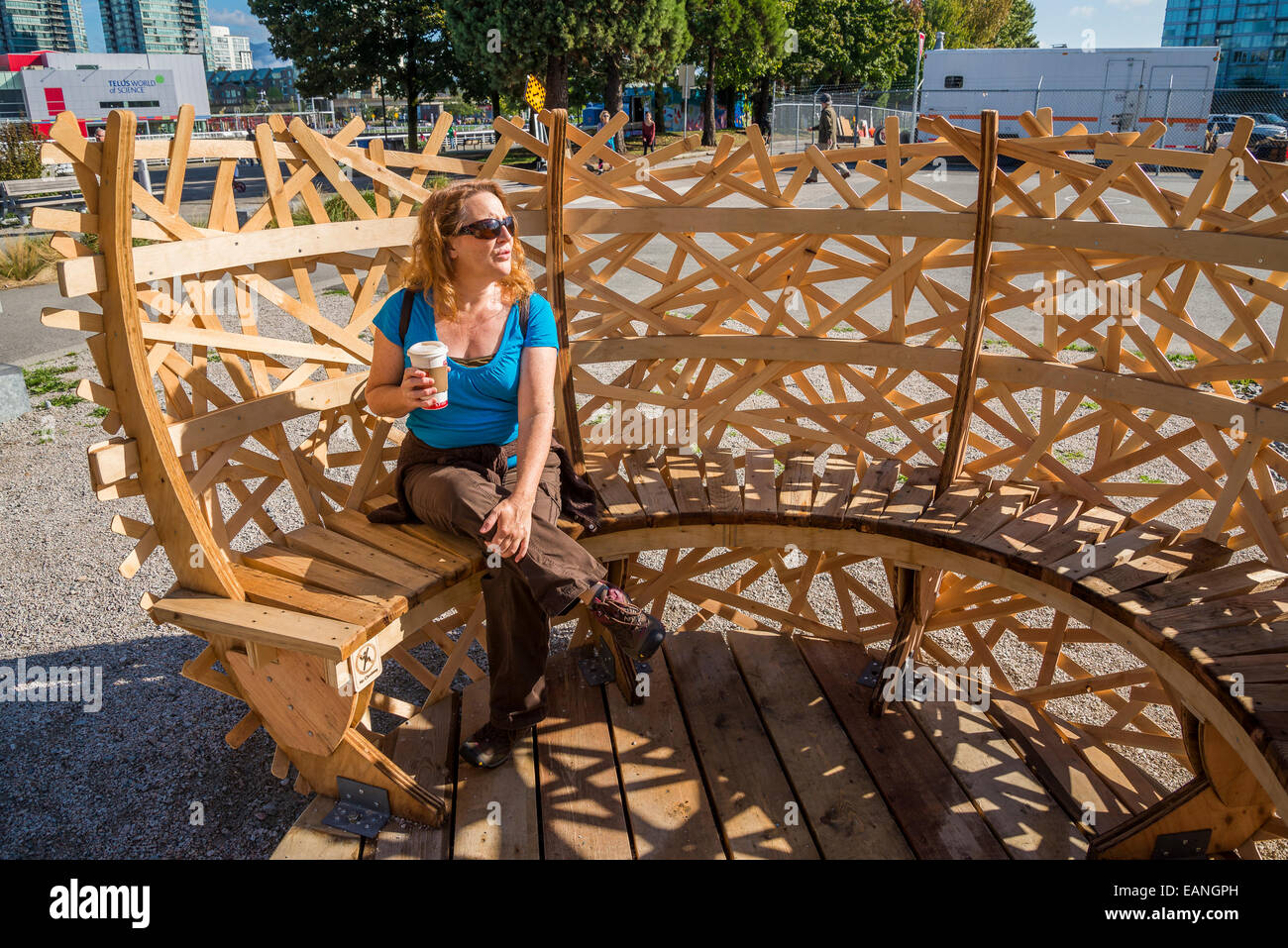 Woman enjoying coffee in spherical lattice enclosed park bench, False Creek, Vancouver, British Columbia, Canada - Stock Image