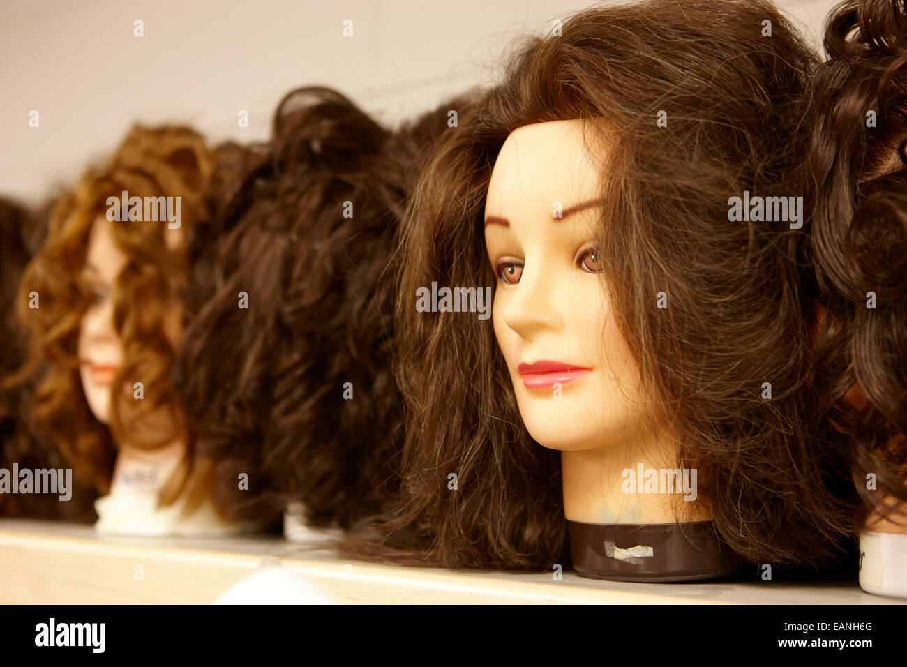 hairdressing practice heads in a training room - Stock Image