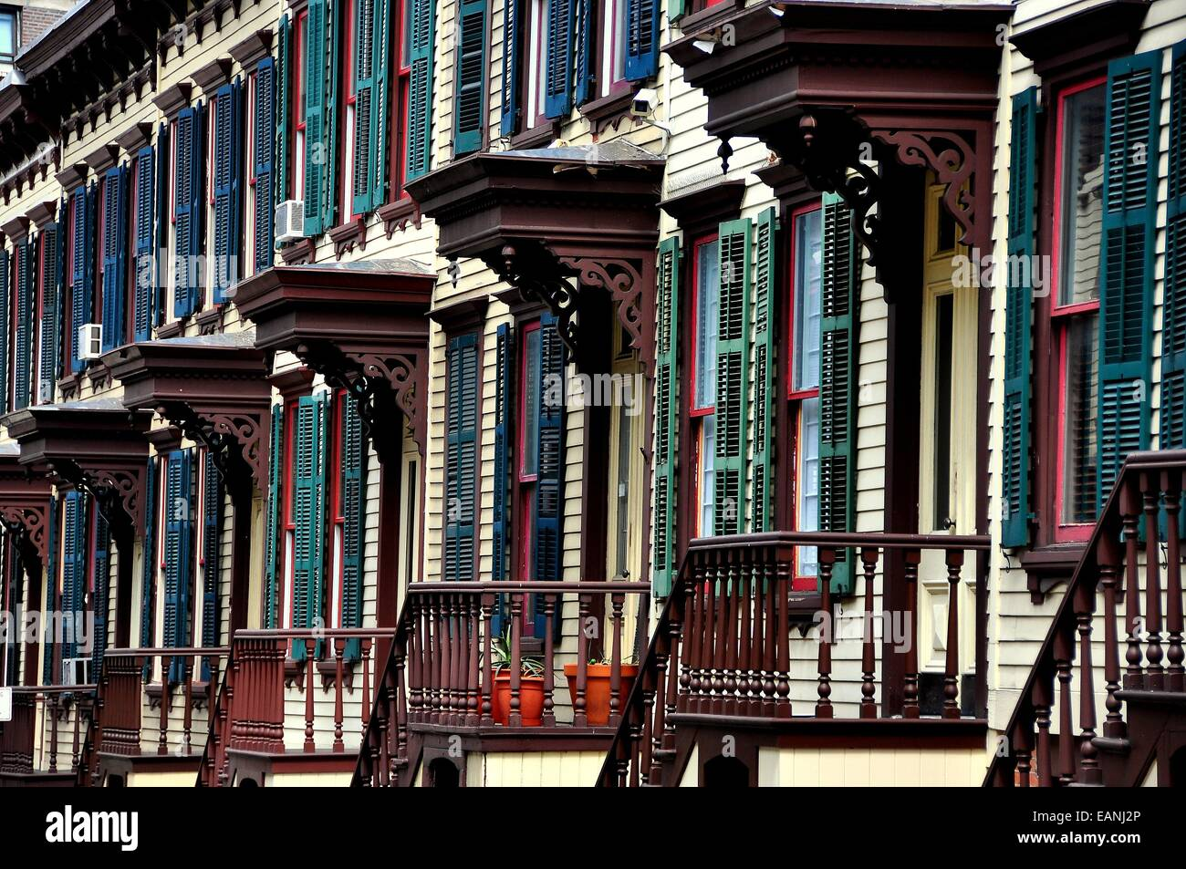 NYC:  1882 two story wooden row houses with shutters, stairway balustrades, and doorway overhangs on Sylvan Terrace Stock Photo