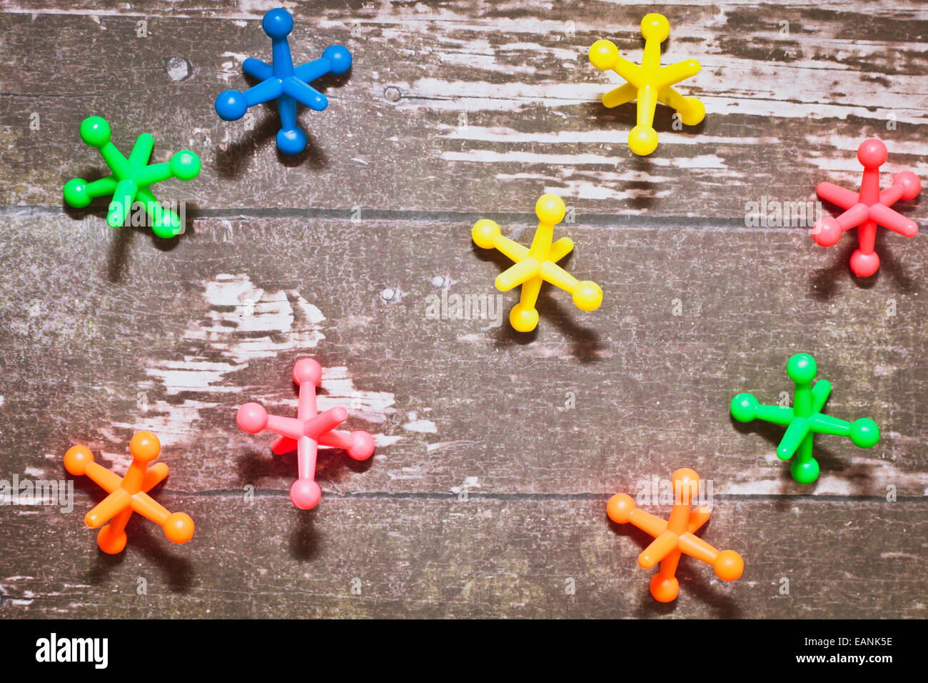 Colorful plastic toys on a wooden surface - Stock Image