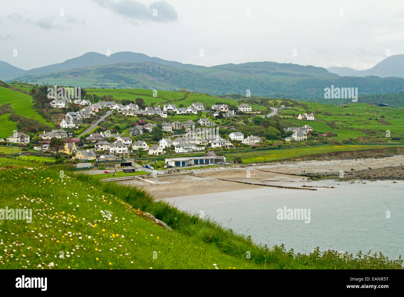 View, from hilltop castle, of Welsh town of Criccieth by beach of Cardigan Bay & green fields stretching to - Stock Image