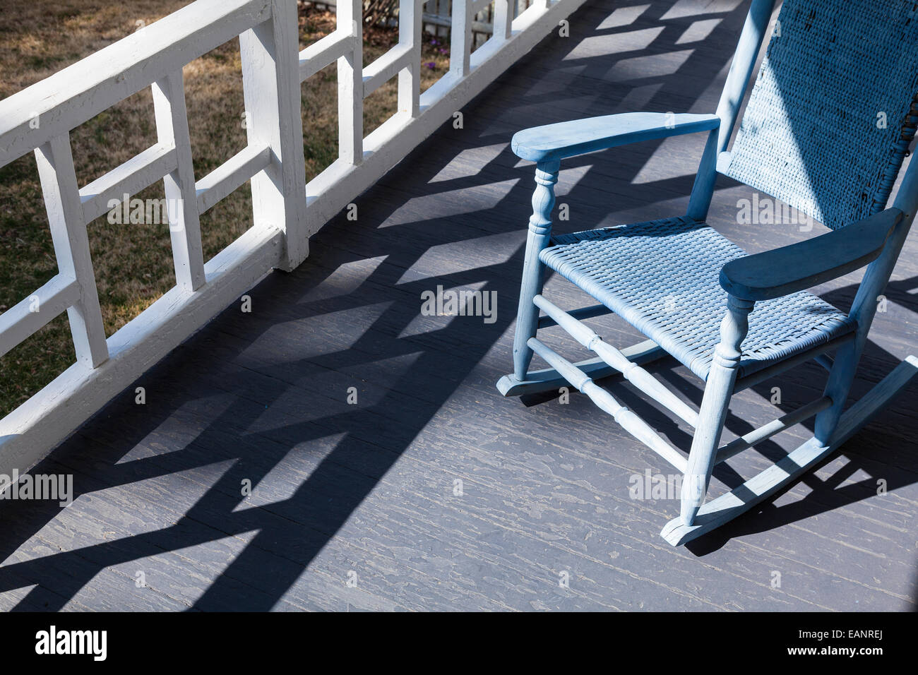 shadows of classic porch railing design make pattern on blue porch decking with rocking chair - Stock Image