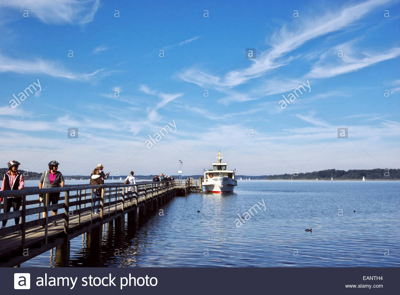 Tourists disembark as others queue up to board an excursion boat for a trip to Herreninsel, an island in the Chiemsee. - Stock Image