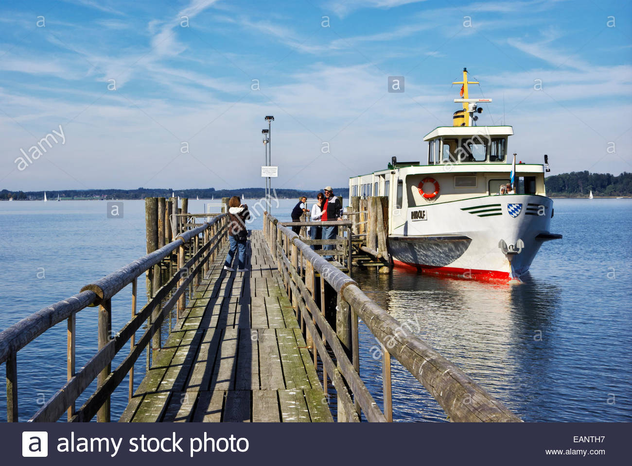 Tourists pause for snapshots before boarding an excursion boat for a trip to Herreninsel, an island in the Chiemsee, - Stock Image