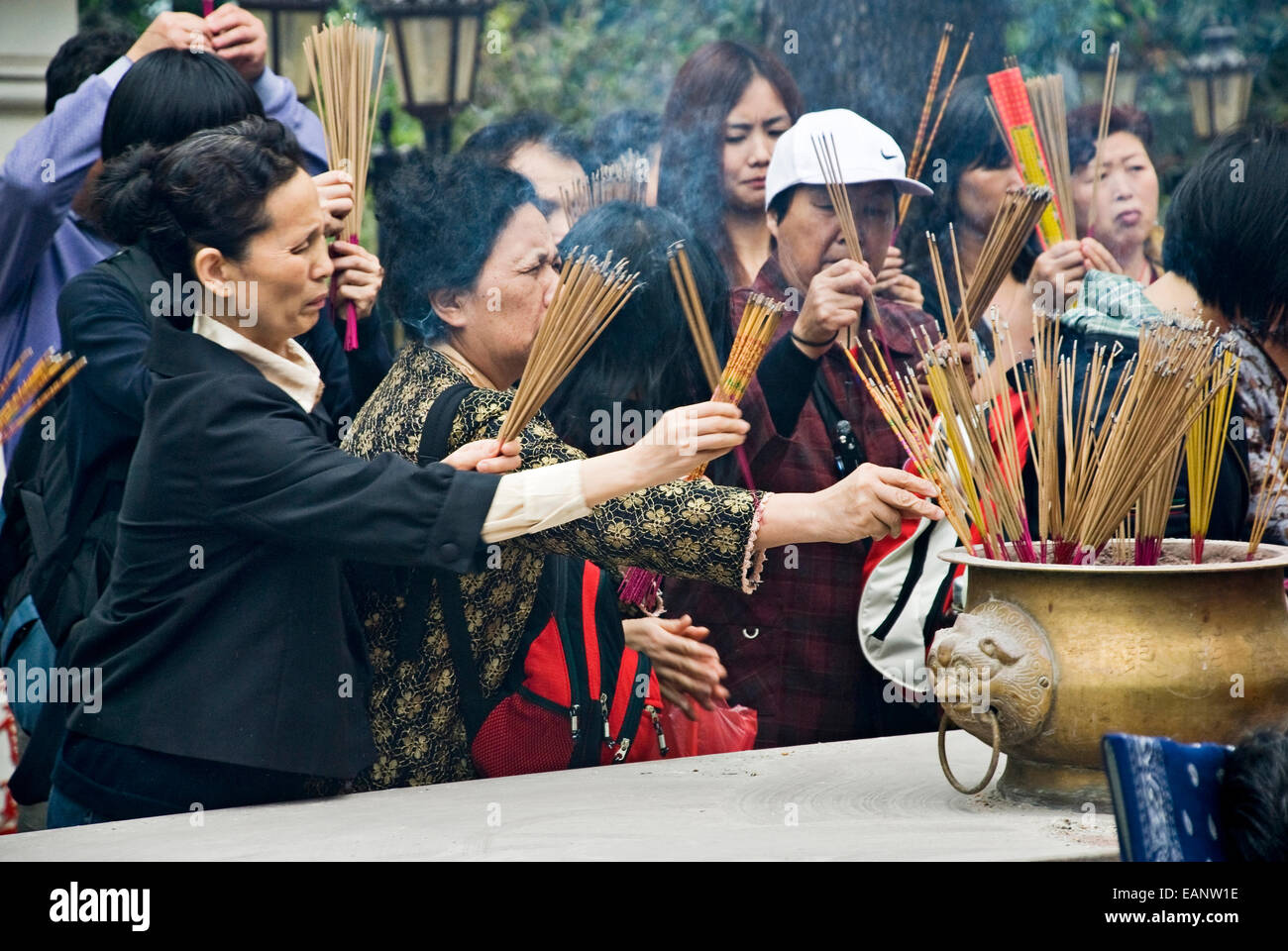 Women lightening incense in the Wong Tai Sin Temple in Kowloon, Hong Kong, China. - Stock Image