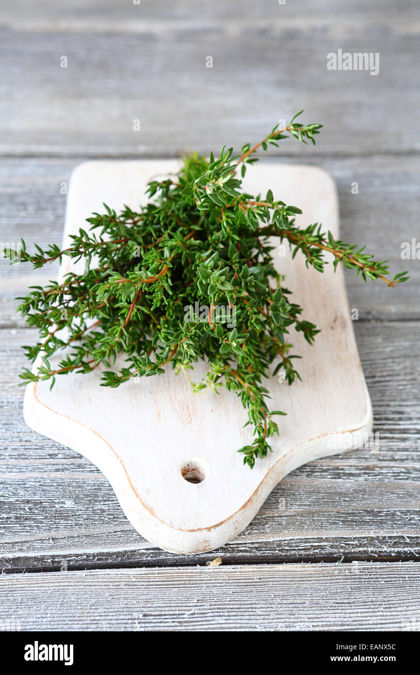 Thyme on cutting board, spice - Stock Image