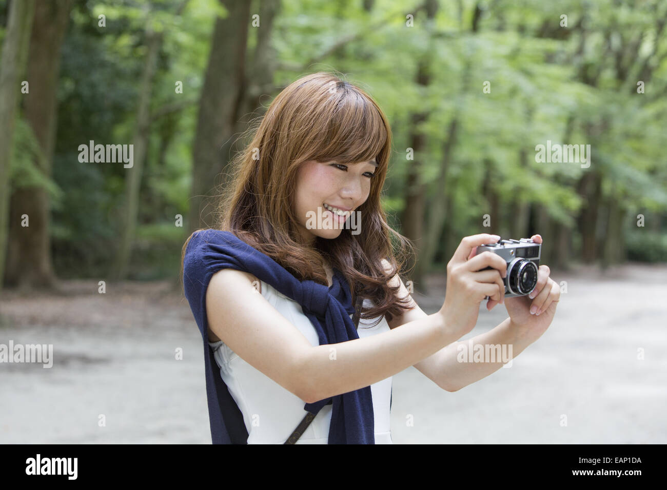 A woman in a Kyoto park holding a camera, preparing to take pictures. - Stock Image