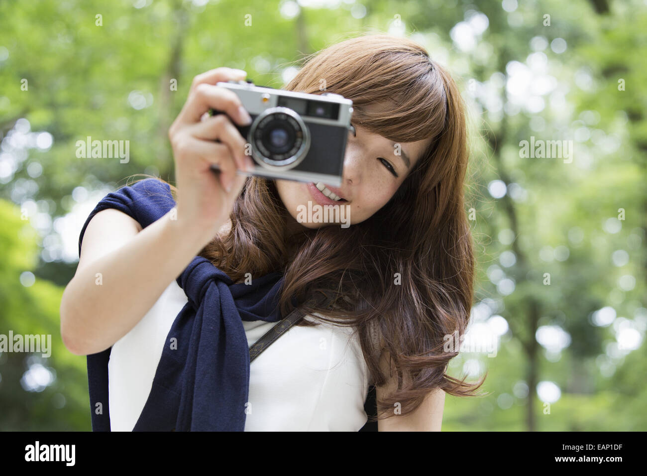 A woman in a Kyoto park holding a camera and laughing. - Stock Image