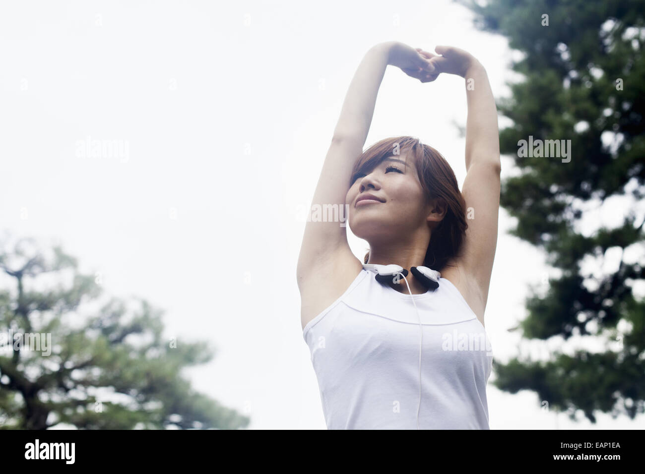 A woman in a Kyoto park, wearing headphones. Wearing jogging kit and stretching before exercise. - Stock Image