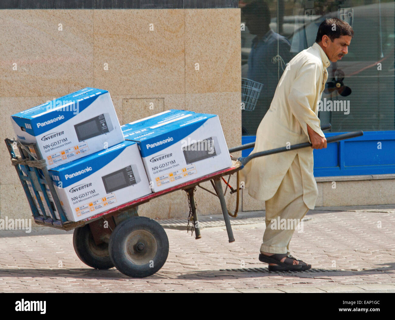 Asian man, migrant worker in traditional dress pulling barrow / trolley loaded with boxes of electronic consumer - Stock Image
