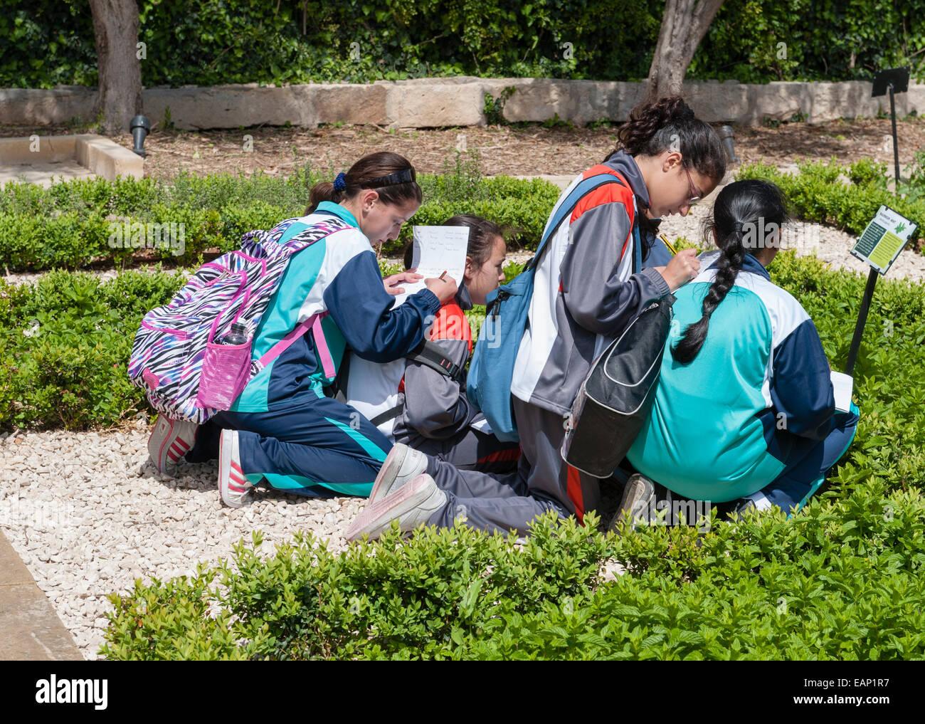 The President's Kitchen Garden, Attard, Malta. Schoolchildren on a botany study trip writing while leaning on - Stock Image