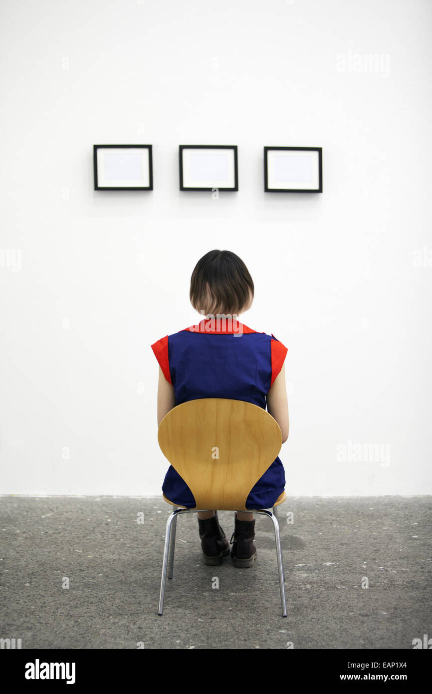 An artist sitting on a chair, looking at an artwork. - Stock Image